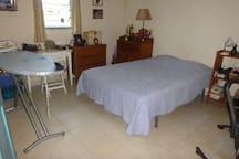 La chambre à lit-double avec le matériel de repassage et un appareil pour faire travailler les muscles