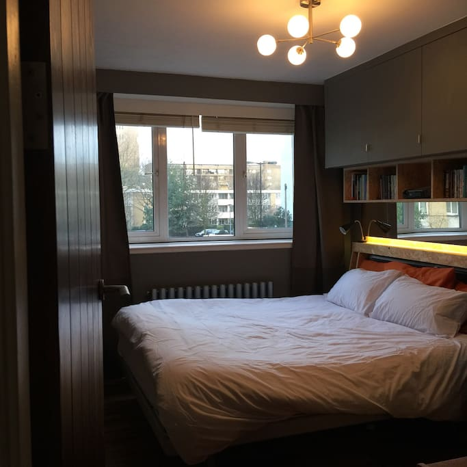 Main (back) bedroom. Comfy king sized double bed. Black-out curtains. Overhead projector and pull down screen is great for films and TV. Plenty of stylish built-in storage, a vintage G-Plan dresser and a fine view of the famous Trellick Tower!
