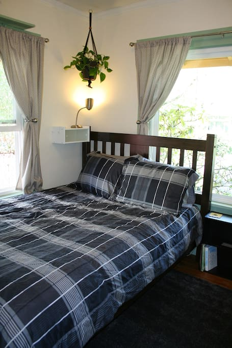 Comfy queen size bed in a well-lit room. When the curtains are closed the room is dark enough to sleep in. Room has 3 lamps for comfortable nighttime lighting.