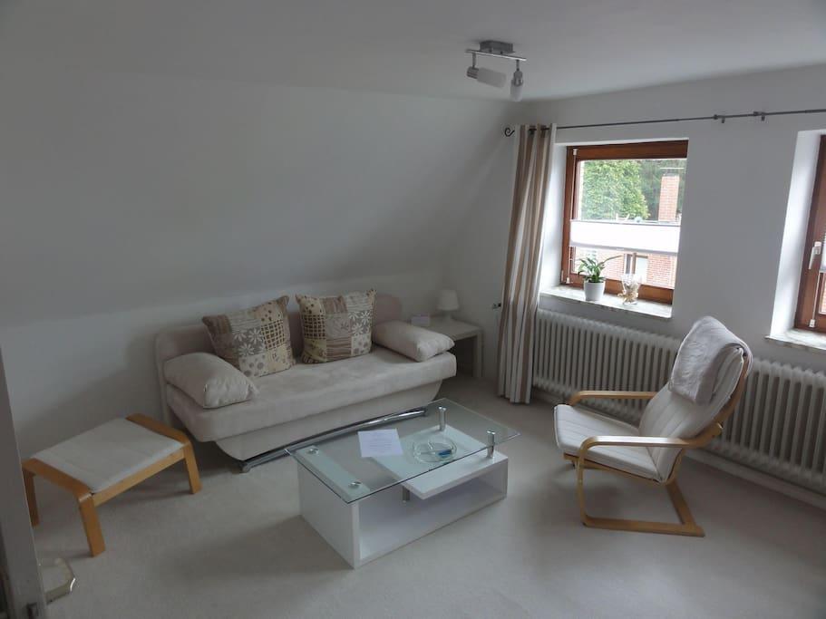 Gemütliches Wohnzimmer mit Couch welches zum 140er Doppelbett wird.