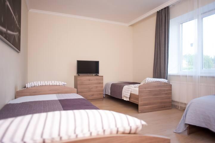 Общий вид комнаты. 4 односпальные кровати, комод телевизор, большое окно с видом на деревню.