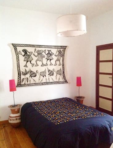 African crafts and colours in your room: the bedside tables are traditional pottery from Niger,  on the wall a bogolan tapestry from Cõte d'Ivoire. The bedspread designed and made by us.