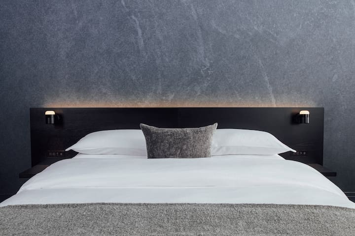 The Lyric signature bed includes a modern headboard design with bedside USB chargers, Casper mattresses, and Frette linens.