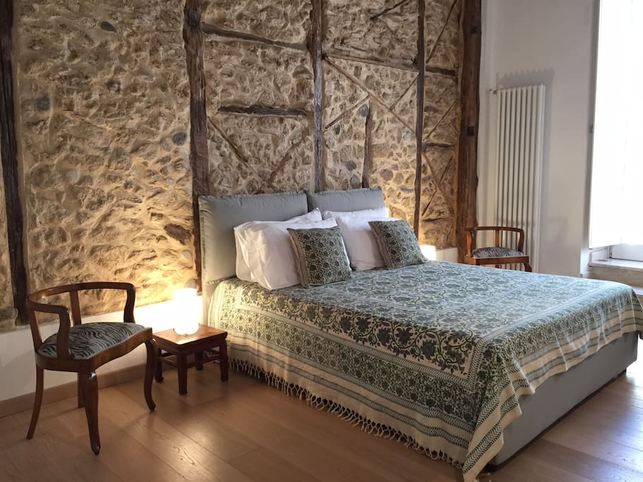 master bedroom with restored stone wall