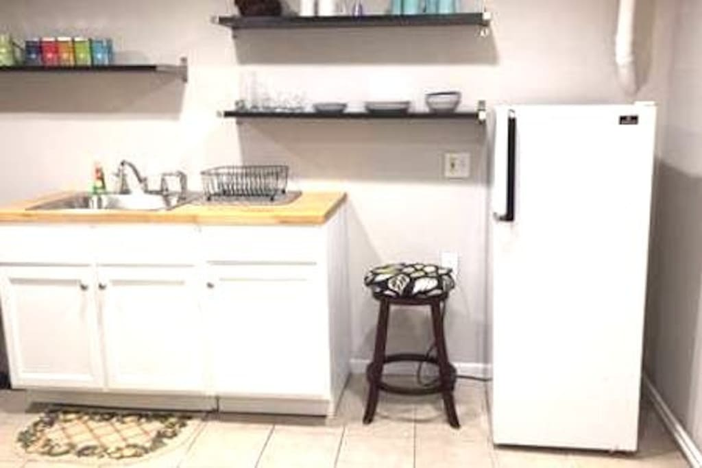 Super cute kitchen with butcher block counter tops, coffee and tea, baking and cooking supplies, oven/stove, fridge, microwave, and dishes for eating in or entertaining!
