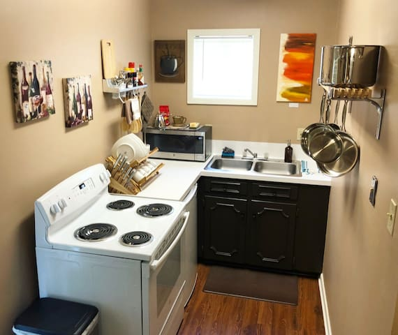 Full kitchen with stove, microwave, mini fridge, and sink.