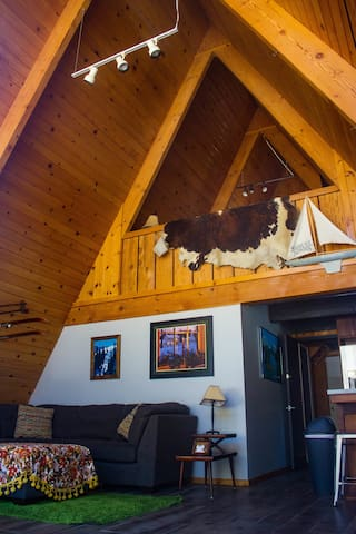 View into main living room area featuring A-frame design. 2-story cabin with bedroom on upper-level of cabin overlooking lower living area.