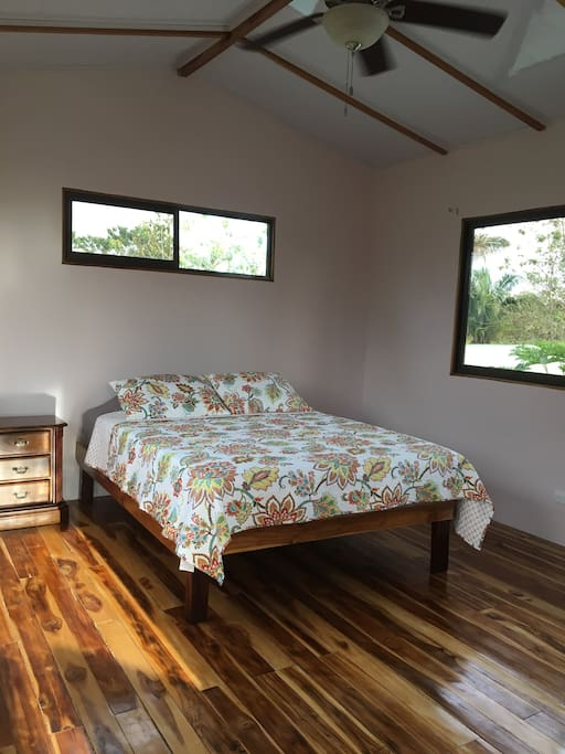 Bedroom is complete with hardwood teak floors, a queen sized bed, an end table, a ceiling fan, a desk, and a single bed if needed.