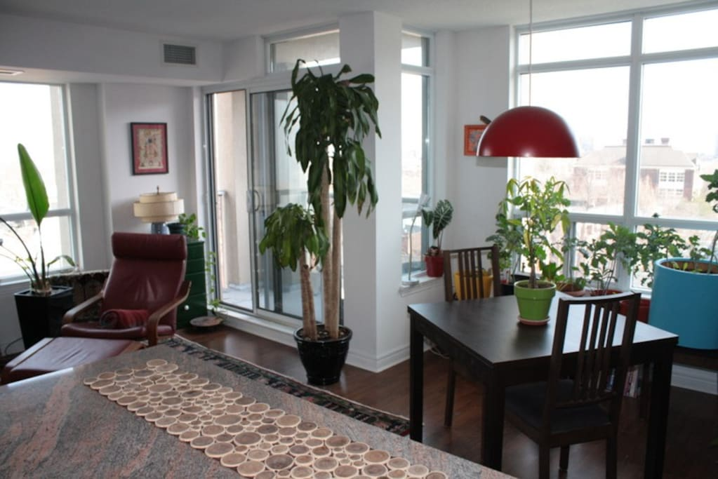 Open concept common spaces as viewed from kitchen counter toward southeast corner and balcony.