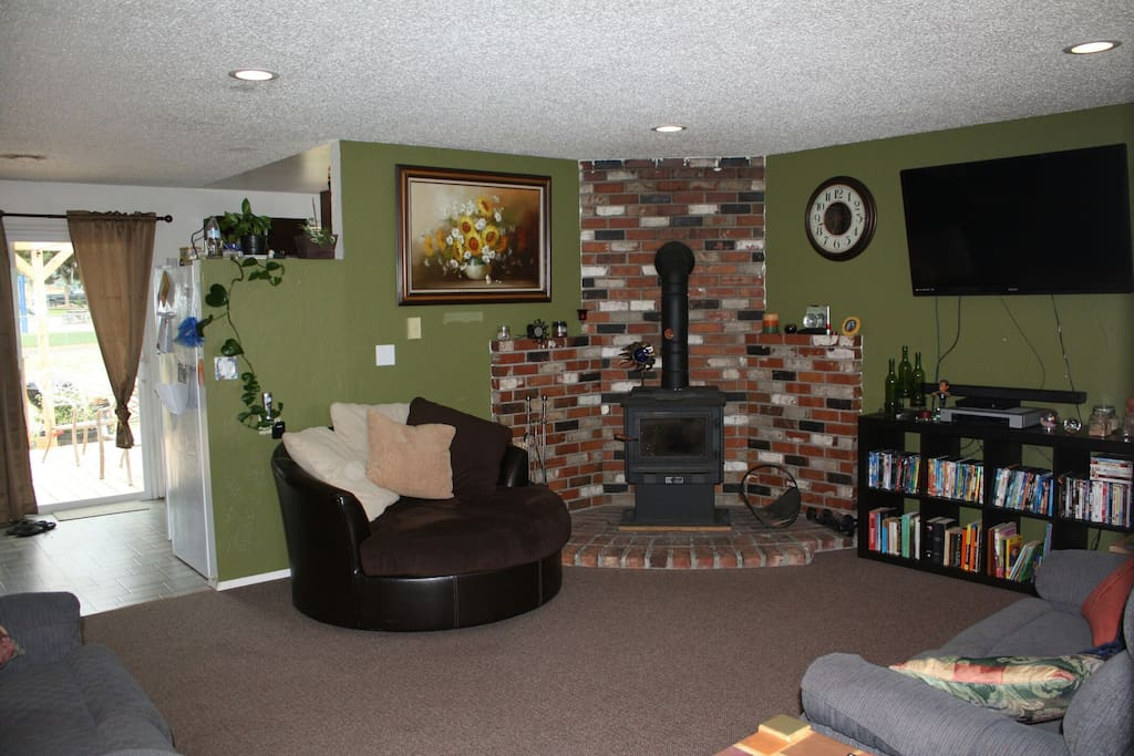 Front room with cozy round couch, wood stove,  4k ultra high def tv and movies.