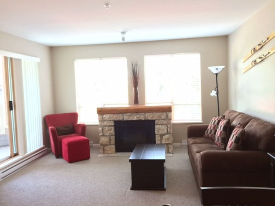 Spacious living room with gas fireplace and access to balcony