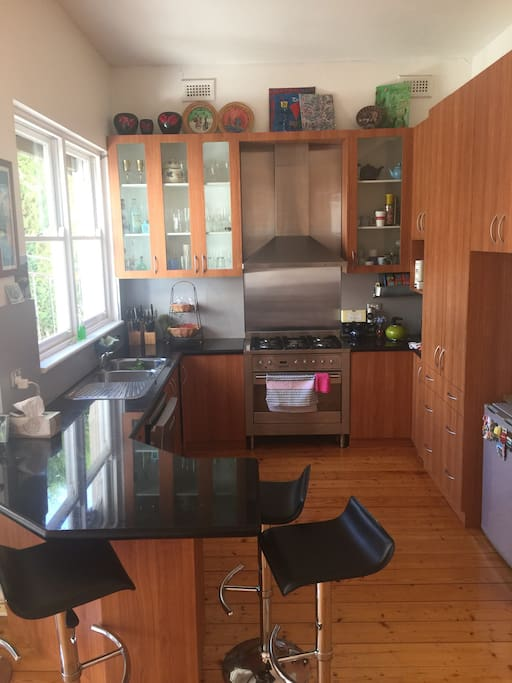 Kitchen facing pool area with gas stove, microwave, dishwasher