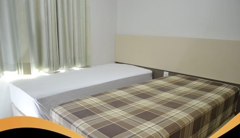 Quarto conta com 2 camas de solteiro podendo uni-las, 1 armário e 1 escrivania.