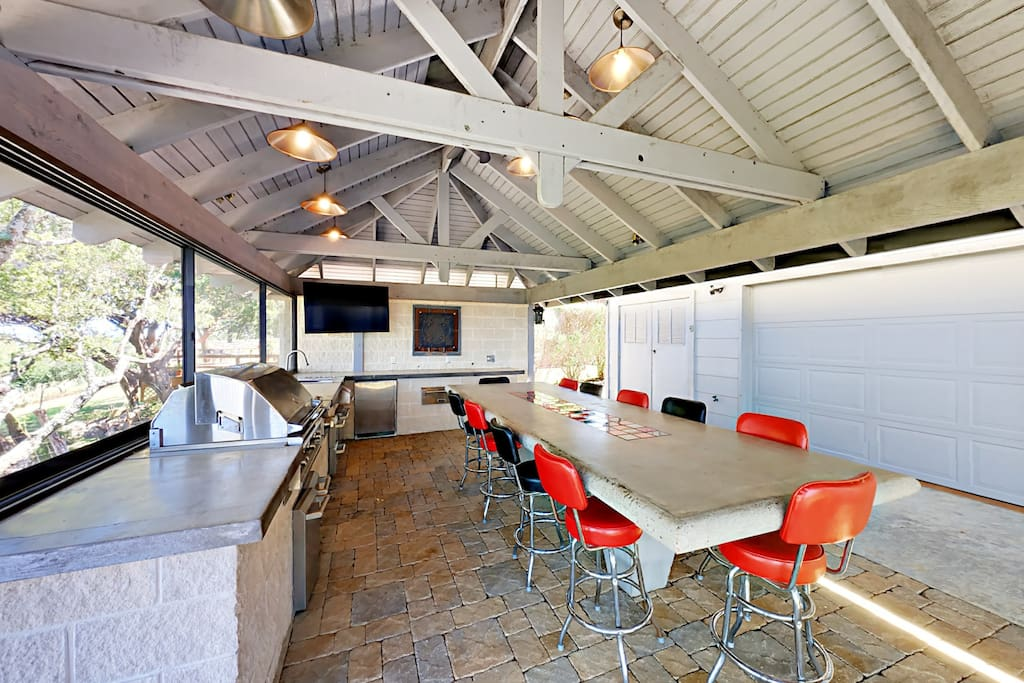 A fully covered outdoor kitchen features an 11-seater concrete dining table