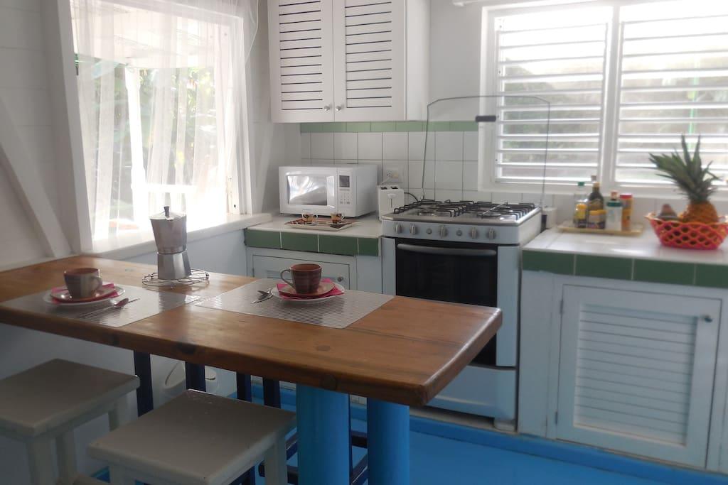 Vue de la cuisine avec la fenêtre passe-plats vers la terrasse.