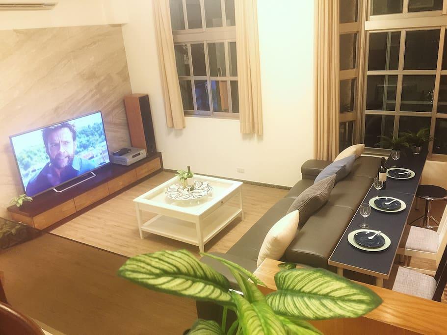 特大的客廳以及電視,客廳後方有早餐桌