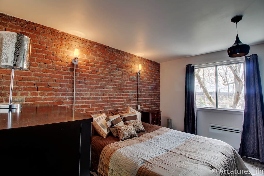 Bedroom #1 -Large bedroom with queen bed, original brick backdrop