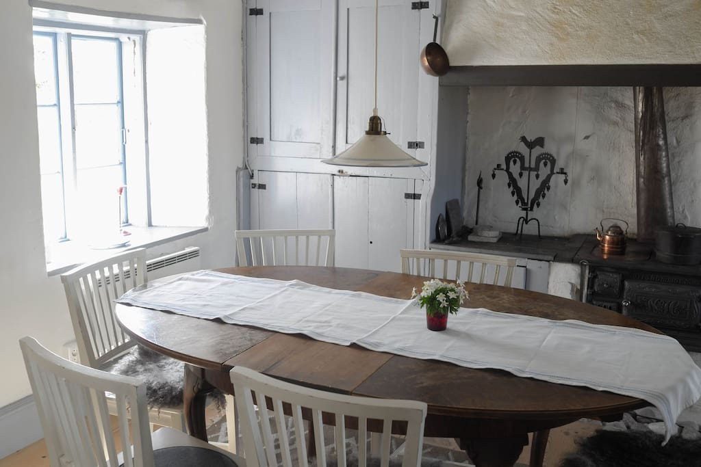 Dining table for 8 people with windows on two sides and an old wood stove.