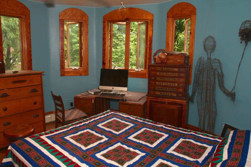 This listing-- North Tower Bedroom with Queen sized bed. Five French windows overlooking the garden. Antique walnut thread cabinet on a Victrola cabinet.