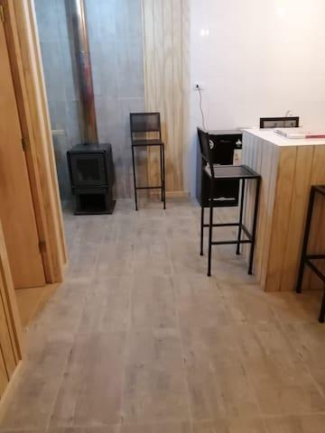 Interior de la cabaña, mesa estufa a leña, refigerador, horno,  encimera