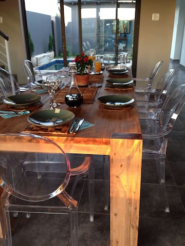 "8- seater farm-style dining table with contemporary ""Ghost "" chairs."
