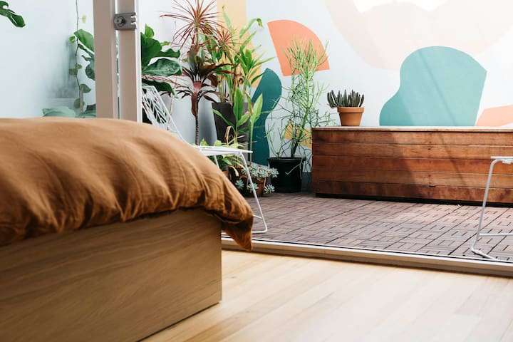 The bedroom doors open up and bring the plant filled terrace into the room.