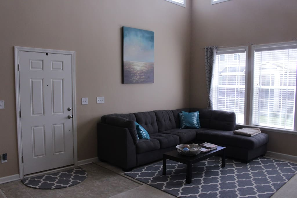First floor has open concept living/dining room space with a sectional.