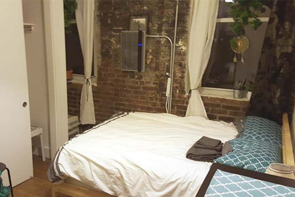 Awesome exposed brick wall of bedroom. Great bed and wall heater.