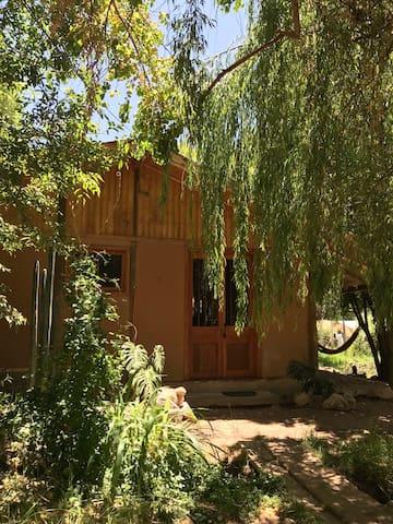 Frente a la casa hay 1 pequeño puente por donde pasa el canal los fines de semana. Hay 1 hermoso sauce llorón y muchas otras plantas alrededor. Las puertas y ventanas de la casa son de madera antiguas recién restauradas.