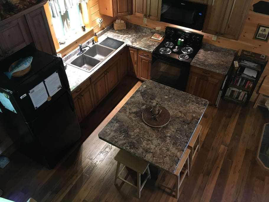 Taken from loft stairs. Six stools surround the island.  Knotty cherry cabinets, complete with Cuisinart coffee maker (coffee & filters included), toaster, all major appliances, fully stocked kitchen.  Feel free to use our condiments, paper products, dish soap, etc.  Night light provided.