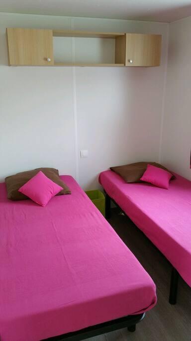 Chambre avec 2 lits d'une personne que l'on peut rapprocher. Fenêtre avec volet roulant