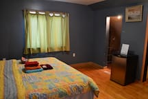 Large room w/ king size bed and small fridge.