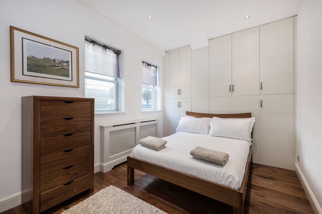 A large master bedroom with a double bed and egyptian cotton linen.American walnut draws and massive amounts of storage.