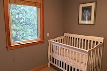 Bedroom #2 has a crib and two single beds.