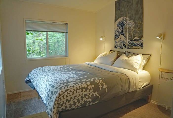Second bedroom, looking out at the woods. Super comfy bed, phone chargers and down comforter.
