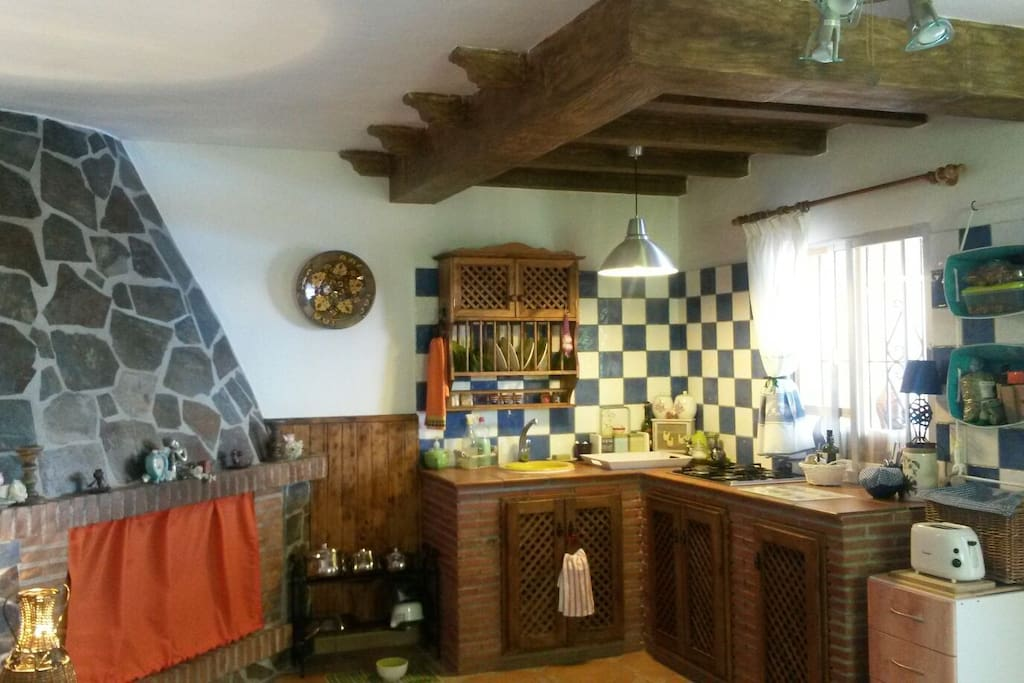 The vibrant cosy kitchen inside the cortijo, you can enjoy the outdoor kitchen and barbeque area!