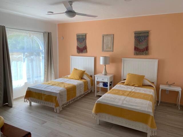 Acogedora habitación para dos personas en camas individuales, cuenta con aire acondicionado, ventilador y closet