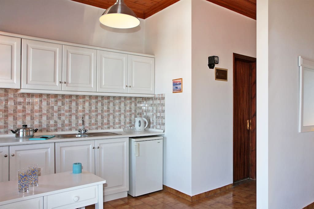 In the same space, the kitchen counter offers small fridge, sink, electric hob with two cooking rings, extractor fan and kettle.