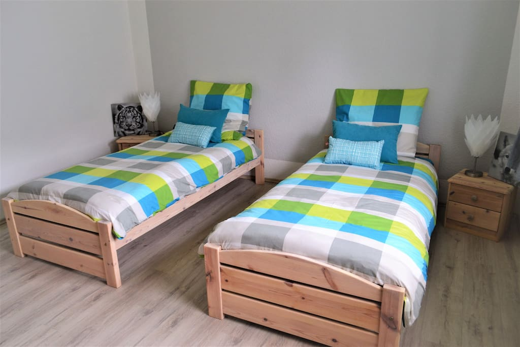Room 1 - with two single beds, bedside tables and a small closet