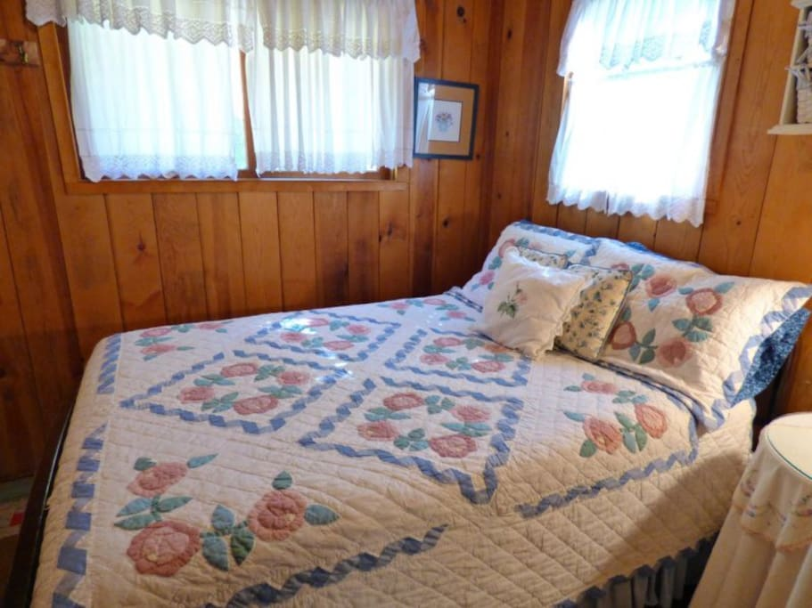 Second bedroom with curtain for privacy has a double bed.