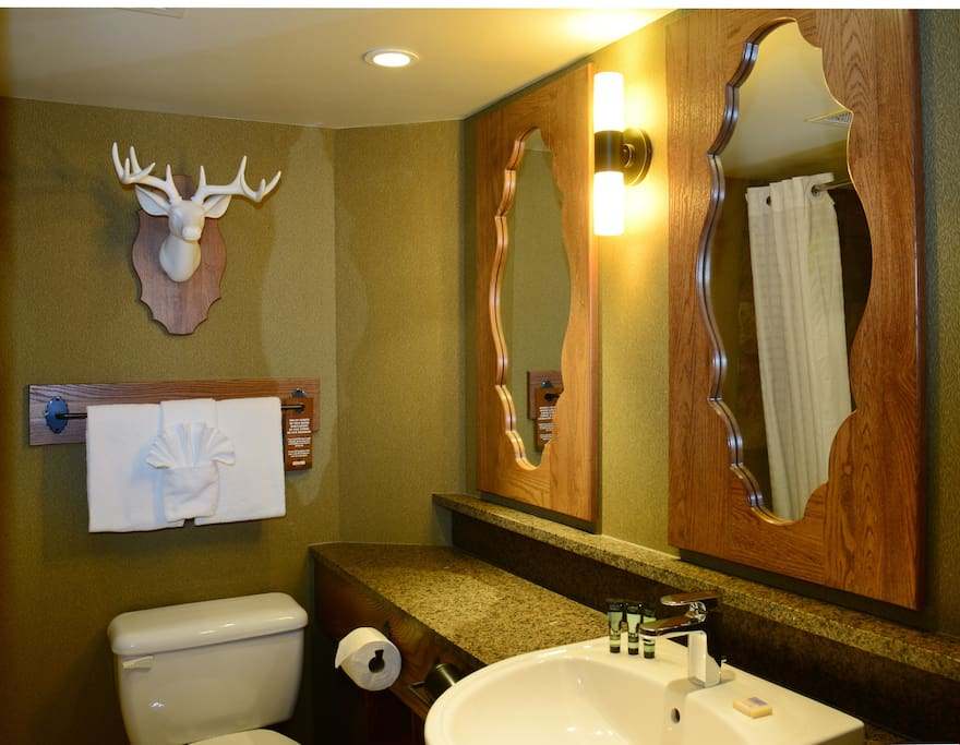 The pristine and spacious bathroom features a shower-tub combination and a beautiful vanity.