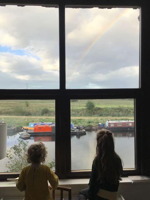Our kids look out of the sitting room at a rainbow