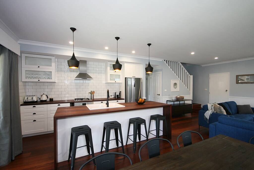 Dining and kitchen with breakfast bar stools.