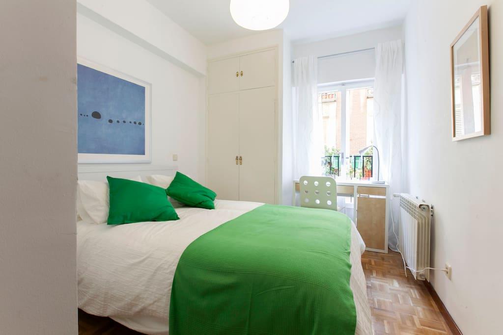 Habitación con cama doble. Mesa de noche y escritorio.