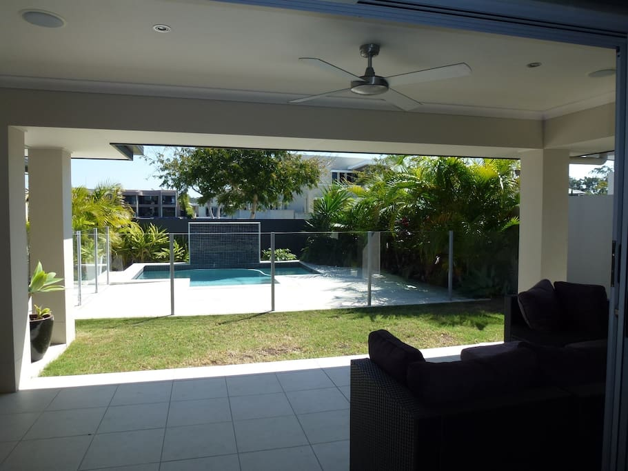 Large private outdoor area facing the fully fenced pool, lounge, fan and integrated speakers.