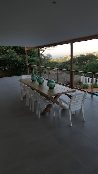 Covered verandah overlooking pool with sea view in the back-ground