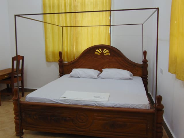Room 4: king size bed with private bathroom, work space and air conditioner