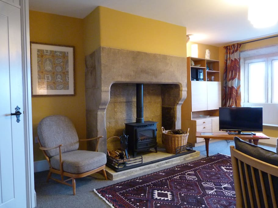 Living room at Elmet Farmhouse with carved stone fireplace and woodburning stove