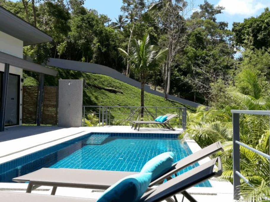 Swimming pool with sunbeds and terrace overlooking the tropical forest