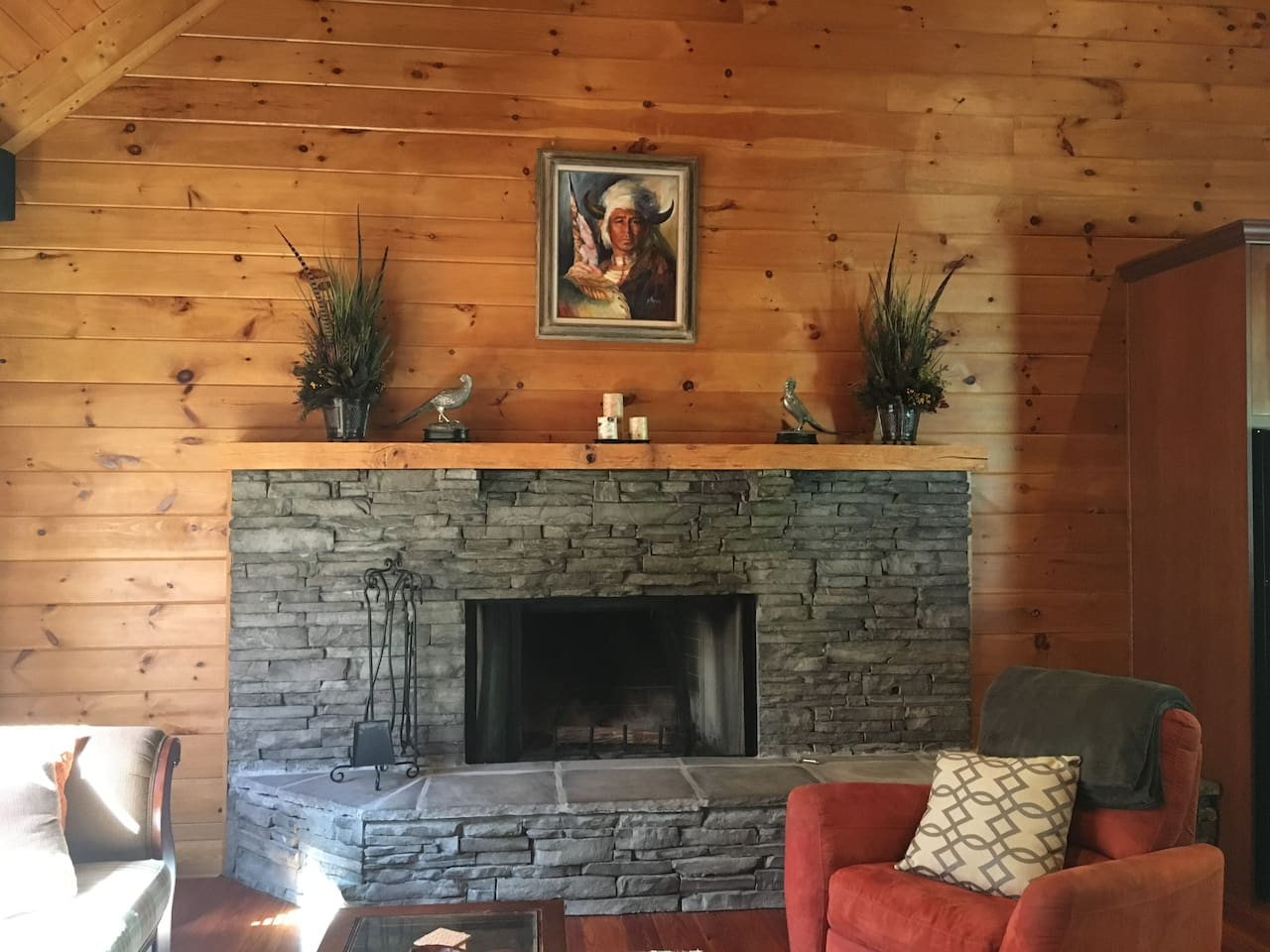 Stacked stone fireplace and hearth in vaulted living room